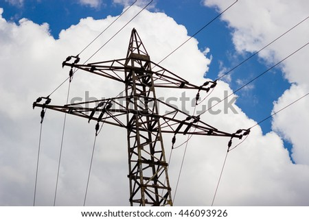 Top of the high voltage tower (electricity post) against sky with big white clouds. - stock photo