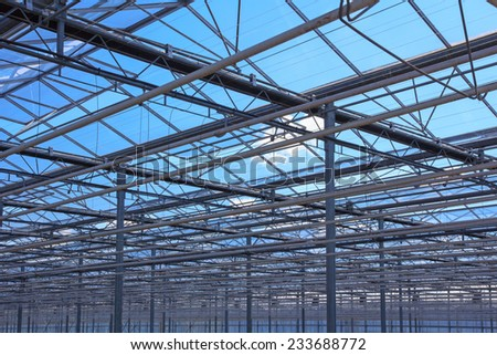 Top of the metal structure of a greenhouse against a blue sky - stock photo