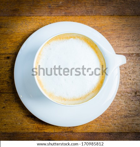 Top of view cappuccino coffee on wood table - stock photo