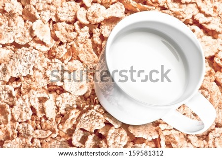 top of view of cup of milk on corn flakes background, diet concept - stock photo