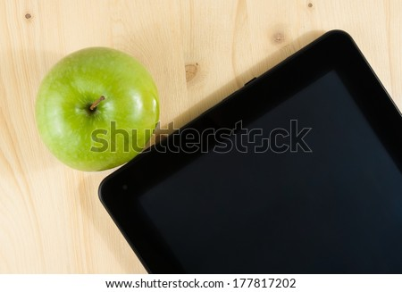 top of view of digital tablet pc and green apple on wood table, concept of learn new technology - stock photo