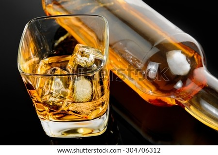 top of view of glass of whiskey near bottle on black table with reflection, time of relax with whisky - stock photo