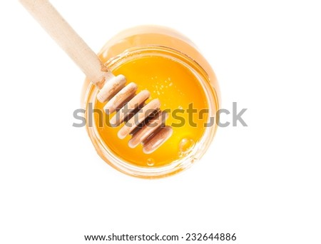 top of view of opened honey jar with wooden honey dipper on top, isolated on white background - stock photo