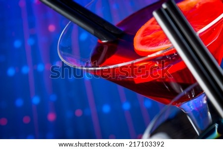 top of view of red cocktail with blue light disco background with space for text, dance disco atmosphere