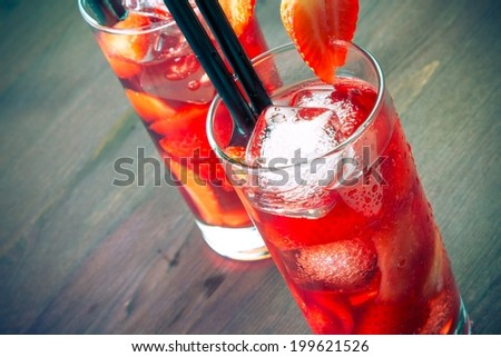top of view of two glasses of strawberry cocktail with ice on old wood table - stock photo