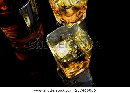 top of view of whiskey with ice in glass on black background, with reflection
