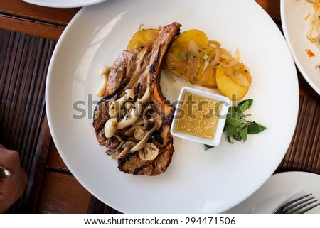 Top of view Pork chop steak on a white plate . Selective focus - stock photo