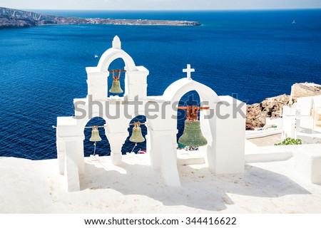 Top of white church and bells, caldera view with blue sea at Oia, Santorini, Greece. - stock photo