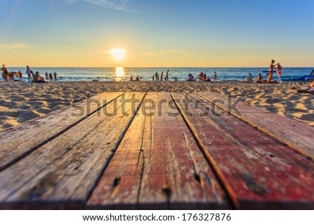 Top of wooden table at sunset beach in Thailand - stock photo
