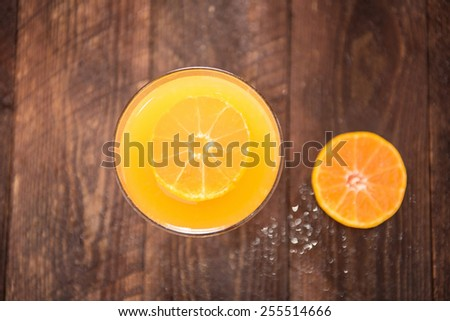 Top orange juice in glass, fresh fruits on wooden background. - stock photo