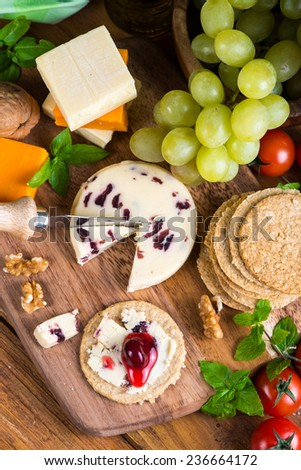 top overhead view on cheese board with grape oat cakes and cranberry - stock photo