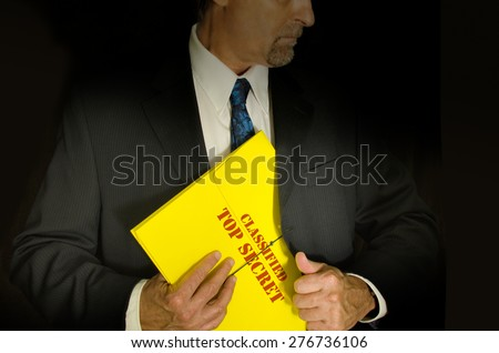 Top Secret Classified business, legal and government concept showing a man in a black suit pulling a Top Secret folder dossier out of his jacket. Dramatic lighting highlights the Top Secret folder - stock photo