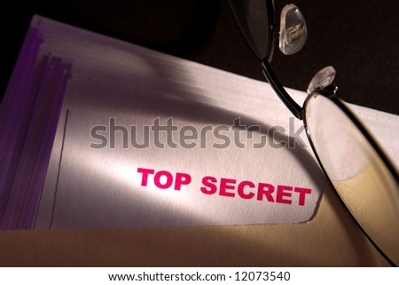 Top secret confidential report inside a file folder with glasses - stock photo