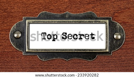 Top Secret - file cabinet label, bronze holder against grunge and scratched wood  - stock photo