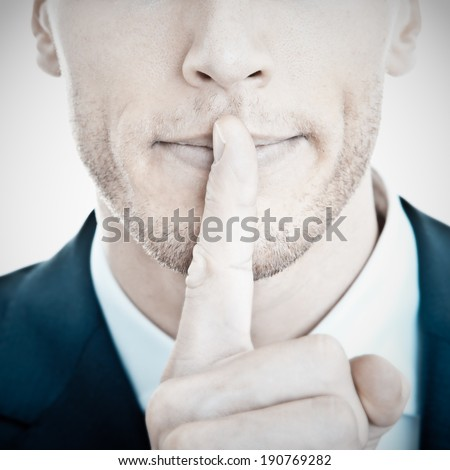 Top secret! - Young businessman with finger on his lips - stock photo