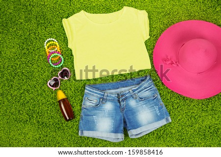 Top, shorts and beach items on bright green background - stock photo