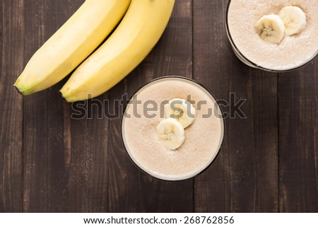 Top shot banana smoothie on wooden table - stock photo