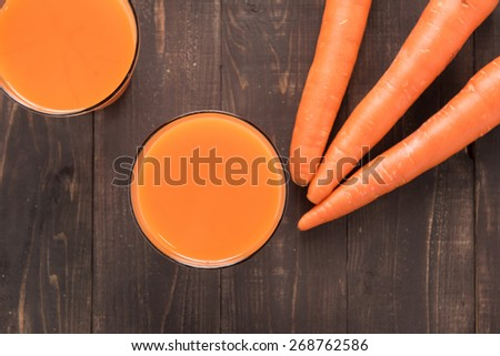 Top shot fresh carrot juice on wooden background. - stock photo
