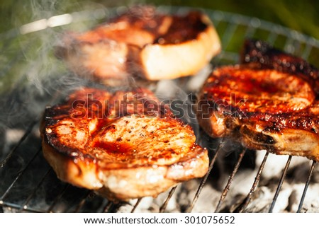 Top sirloin steak on a barbecue, shallow depth of field. Summer BBQ closeup, outdoor grill concept. Grilled steak meat cooked on carocal.