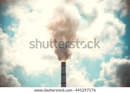top tube factory with smoke from it against the sky with a bright sunlit white clouds, filter
