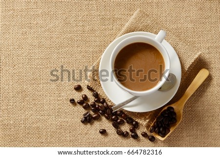 Top view, A cup of coffee with coffee beans on sack background