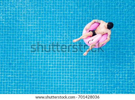 Top View, A Man Relaxing On Pink Flamingo Swim Pool Float, On Swimming Pool