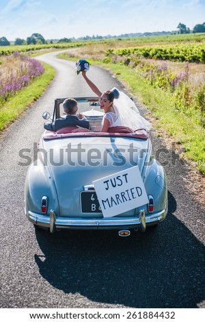 Top view, a newlywed couple is driving a retro car, the bride is looking at camera with her bouquet. - stock photo
