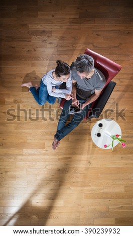Top view, A  stylish couple sitting in the living room using a digital tablet, man sits in an armchair, the woman on the wooden floor. A little table with flowers and two cups of coffee near them - stock photo