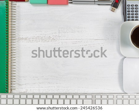 Top view angle of a white wooden desktop with border of business office objects consisting of computer, mouse, pencil, pen, eraser, spiral notepad, coffee, calculator and thumb drive.  - stock photo