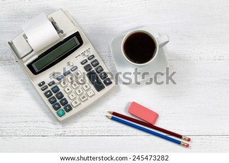 Top view angle of a white wooden desktop with old fashion calculator and paper tape, cup of coffee, pencils and eraser. - stock photo