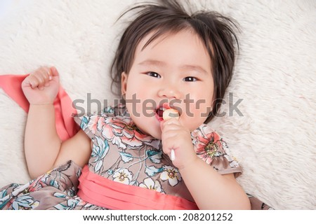 Top view angle of an funny baby girl with a sweet candy - stock photo