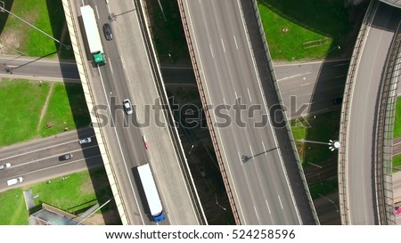 Top view at curves and lines of city highway. Two semitrailer trucks drive on road. Summer. Russia