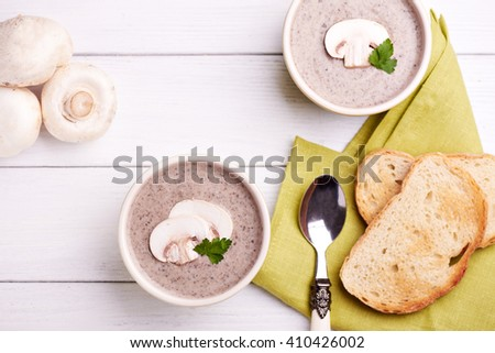 Top view at delicate cheese cream soup with mushrooms and crispy bread on a table - stock photo