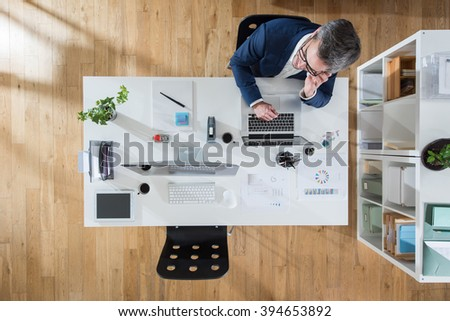 Top view at office. A grey hair businessman sitting at his desk and working on a laptop.Focus is on the table - stock photo