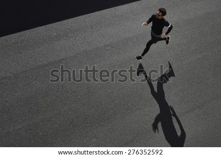 Top view athlete runner training at road in black sportswear at central position. Muscular fit sport model sprinter exercising sprint on city road. Full body length of Caucasian model. - stock photo