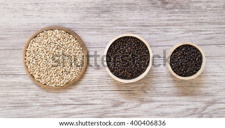 Top view - Beer ingredients, Pale ale malt ,Chocolate malt and Roast malt  on wooden background - stock photo