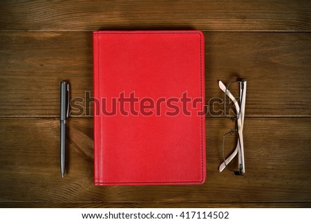 top view blank red leather diary, glasses and pen on wooden desk - stock photo