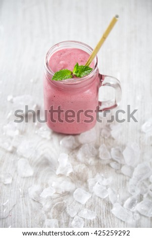 Top view close focus rustic jar with cold fresh berry smoothie isolated on wooden table with golden straw inside surrounded with crashed melted ice cubes Summer healthy refreshment drink