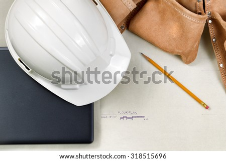 Top view close up of construction contractor tools on top of blue print drawings.   - stock photo