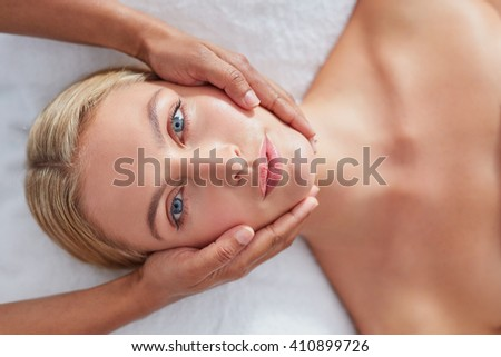 Top view close up shot of a relaxed woman on massage table enjoying beauty treatment at spa - stock photo