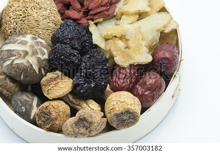 Top view closeup on assortment of Chinese herbal soup ingredients in a bamboo bowl focusing on the black dates at the center, blurring out other ingredients.  Isolated on white background. - stock photo