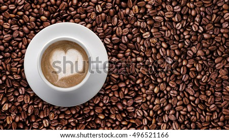 Top view- Coffee cup of LATTE ART, Love symbol, lover sign on Pile of roast coffee beans with copy space for text or graphic design. Cafe' latte cream in heart shape on background of raw coffee.