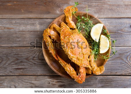 Top view cooked delicious hot and spicy sauce blue crab, on wooden background. Fresh cook with hot smoke steams. - stock photo
