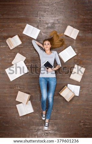 Top view creative photo of beautiful young woman on vintage brown wooden floor. Girl lying near books and holding tablet computer - stock photo