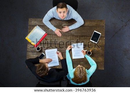 Top view creative photo of business people sitting at dark wooden vintage table. Employers having meeting. Concept for interview. Employee looking at camera - stock photo