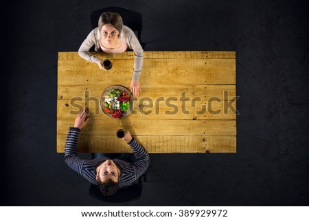 Top view creative photo of couple sitting at wooden vintage table. Man and woman having romantic dinner. They with cheese plate and glasses with wine. Couple looking at camera - stock photo