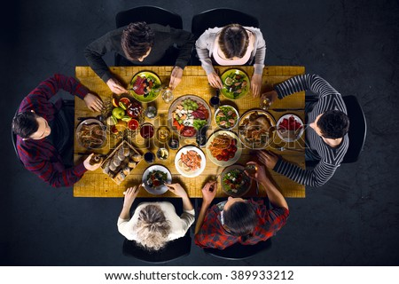 Top view creative photo of friends sitting at wooden vintage table. Friends of six having dinner. They with plates full of delicious meal and glasses with drinks - stock photo