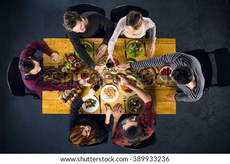 Top view creative photo of friends sitting at wooden vintage table. Friends of six having dinner. They with plates full of delicious meal and glasses with drinks. All clinking glasses - stock photo