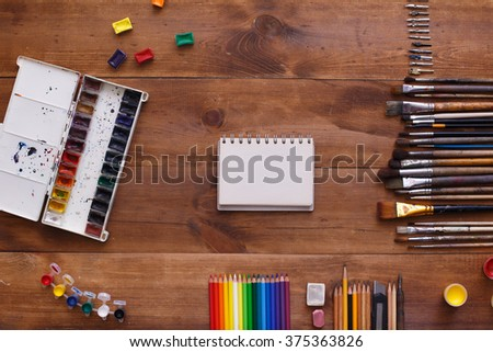 top view designer workplace. Desk of an artist with lots of stationery objects. Studio shot on wooden background. - stock photo