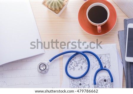 Top view doctor office with cup of coffee,stethoscope, ekg paper, blood test exam and  blank document